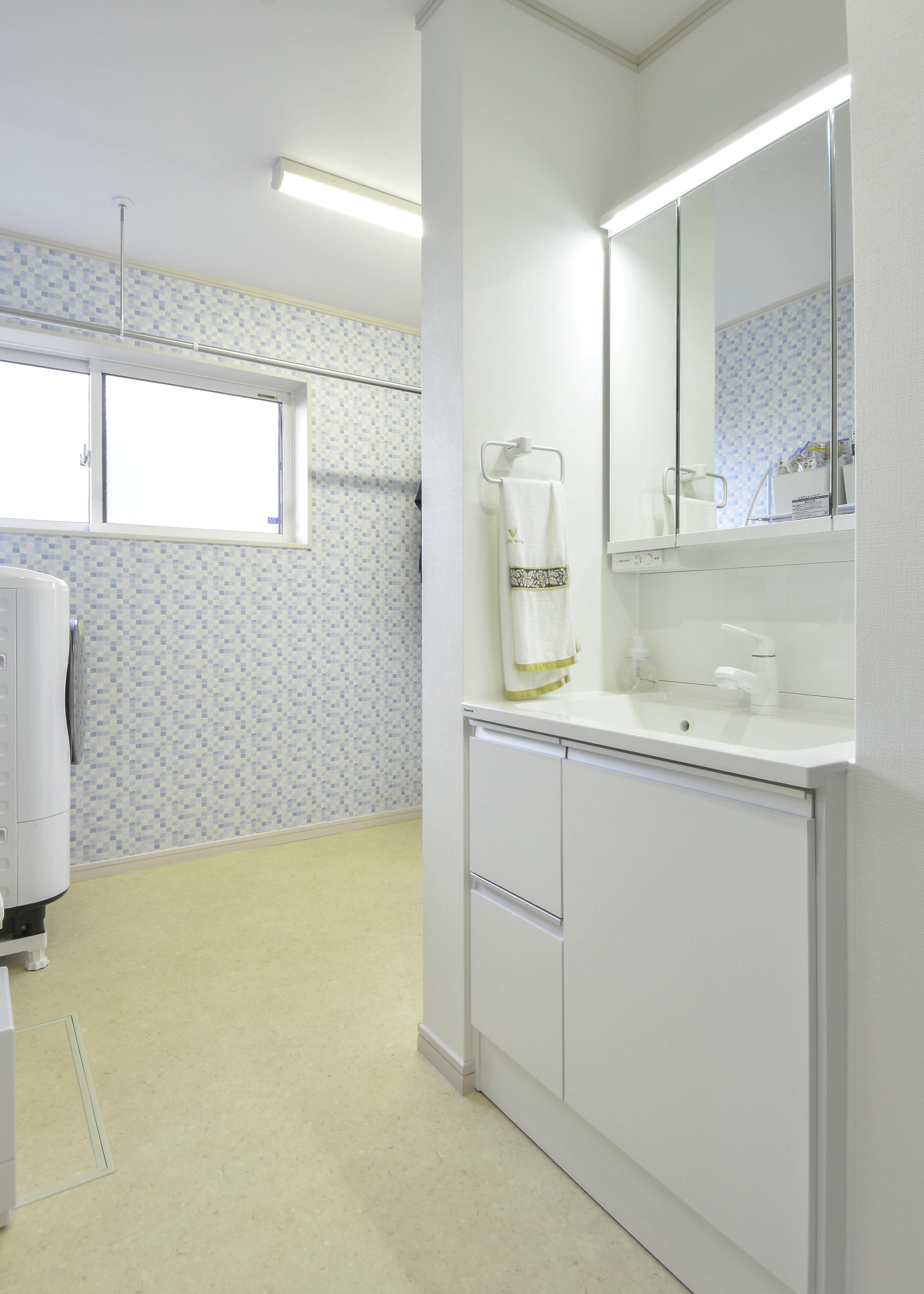 爽やかな壁紙ランドリースペースへ続く洗面所へ大変身